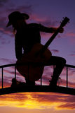 Silhouette cowgirl kneel with guitar look back. A silhouette of a woman kneeling on a bridge holding on to her guitar royalty free stock images