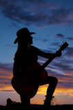 Silhouette cowgirl kneel with guitar look side. A silhouette of a woman kneeling on the ground in the outdoors holding on to her guitar royalty free stock images