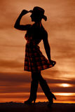 Silhouette cowgirl side hold skirt hat. A silhouette of a woman standing holding out her checkered skirt and touching the brim of her cowgirl hat Royalty Free Stock Photos