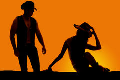 Silhouette cowgirl sit twist to look at cowboy Stock Images