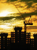 Silhouette of crane and building construction and sun set sky wi Royalty Free Stock Images
