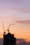Silhouette of crane on building construction. Silhouette of crane and building construction at sunset Royalty Free Stock Photography