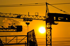 Silhouette crane building and sunset Stock Photography