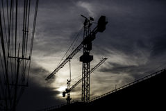 Silhouette of crane on building with sunset sky. Background Royalty Free Stock Photo