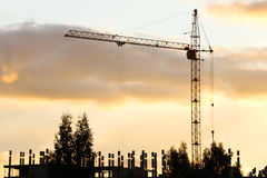 Silhouette of crane and building under construction in evening Stock Photos