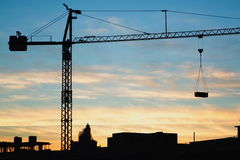 Silhouette crane in city. Scenic view of silhouetted crane lifting object over city skyline, sunset and cloudscape background Stock Photos