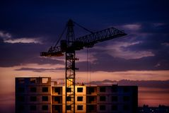 Silhouette of crane and construction at sunset. Silhouette of crane and construction with the worker at sunset Stock Photo