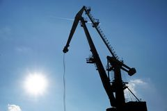Silhouette of crane on port. With blue sky in background Royalty Free Stock Photos