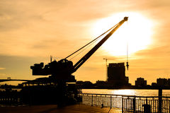 Silhouette crane working at port with sunset in Bangkok, Thailand.  Royalty Free Stock Images