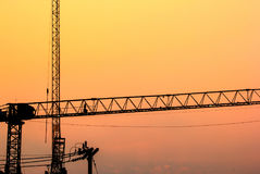 Silhouette cranes at construction side with the twilight sky Royalty Free Stock Photos