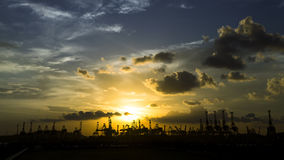 Silhouette of cranes at harbor during sunset. Royalty Free Stock Photography