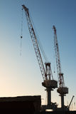 Silhouette of Cranes at Work in Boatyard Royalty Free Stock Photos