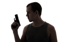 Silhouette of criminal man holding gun isolated on white Royalty Free Stock Images