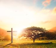 Silhouette croisée noire conceptuelle de symbole de religion de concept dans l'herbe au-dessus du coucher du soleil ou du ciel de Photos stock