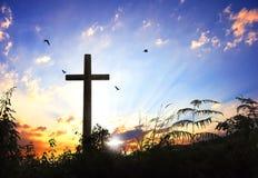 Silhouette croisée noire conceptuelle de symbole de religion de concept dans l'herbe au-dessus du coucher du soleil ou du ciel de Photographie stock libre de droits