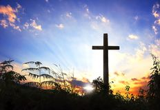 Silhouette croisée noire conceptuelle de symbole de religion de concept dans l'herbe au-dessus du coucher du soleil ou du ciel de Photos libres de droits