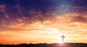 Silhouette croisée noire de symbole de religion dans l'herbe au-dessus du coucher du soleil ou du ciel de lever de soleil photos stock