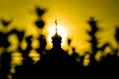 The silhouette of the cross and church bell tower in sunrise stock images