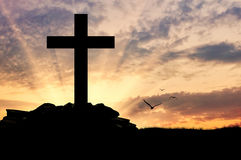 Silhouette of a cross. Concept of religion. Silhouette of a cross in beams of light at sunset Royalty Free Stock Images