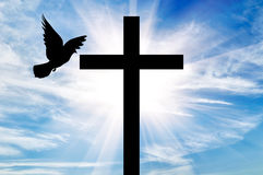 Silhouette of a cross and dove. Concept of religion. Silhouette of a cross and dove in the rays of light on the background of the beautiful sky stock photography