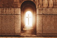 Silhouette of the cross at the end of tunnel with ray of light. Silhouette of the cross at the end of tunnel with ray of sunlight behind Stock Image