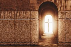 Silhouette of the cross at the end of tunnel with ray of light. Silhouette of the cross at the end of tunnel with ray of sunlight behind Stock Photos