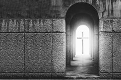 Silhouette of the cross at the end of tunnel with ray of sunligh. T behind in white tone Royalty Free Stock Photography