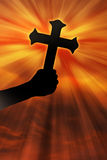Silhouette of Cross Held up at Sunset Royalty Free Stock Image