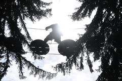Silhouette crossing the void. People in silhouette crossing the void on a tree trail Stock Photos