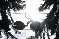 Silhouette crossing the void. People in silhouette crossing the void on a tree trail Stock Image