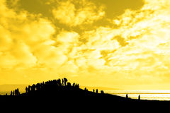 Silhouette of a crowd on a hill. A silhouette of a crowd on a hill with a view of the sea and sunset Royalty Free Stock Images