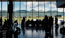 Silhouette crowd people waiting for airplane in terminal with mountain background Stock Images