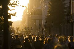 Silhouette crowd of people walking down the street at summer sunset. Telephoto shot royalty free stock images
