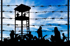 Silhouette crowd  refugees on ground. Concept of refugee. Silhouette of a crowd of refugees rest on the ground near the fence or barbed wire and watchtower Stock Photo