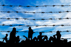 Silhouette  crowd of refugees rest on  ground. Concept of refugee. Silhouette of a crowd of refugees rest on the ground near the fence or barbed wire Stock Images
