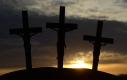 Golgotha mountain. Silhouette of 3 crucified humans in the evening light stock photos