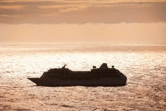 Silhouette of a cruise ship. On voyage at dusk Stock Photos