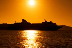 Silhouette of cruise ship with sunset at sea.  Stock Photos