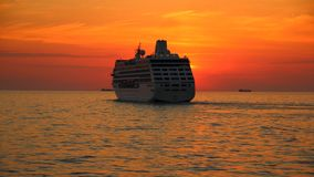 Silhouette of a cruise ship at sunset Stock Image