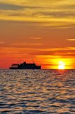 Silhouette of a Cruise at sunset. Sun setting with silhouette of big cruise royalty free stock photo
