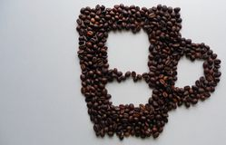 Silhouette of Cup with coffee beans on white background stock images