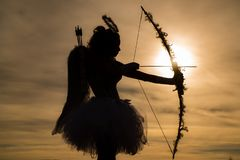 Silhouette of a cupid. Side view of teen girl archer against sunset. Cupid in valentine day - Valentine concept. stock photo