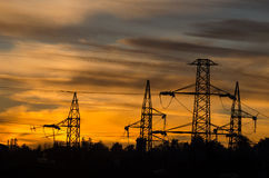 Silhouette of current cables at sunset Stock Photo