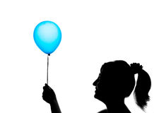 Silhouette of a cute young girl with blue balloon Stock Image