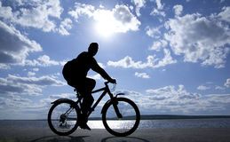 Silhouette of cyclist. In motion on the background of a beautiful blue sky Stock Photo