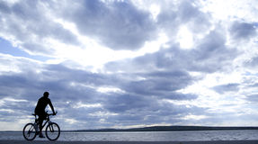 Silhouette of cyclist. In motion on the background of a beautiful blue sky Royalty Free Stock Photos