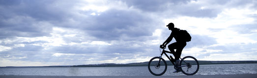 Silhouette of cyclist. In motion on the background of a beautiful blue sky Stock Photography