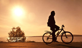 Silhouette of the cyclist. Who rides a bicycle with no hands Stock Photo