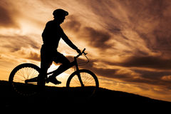 Silhouette of cyclist against sunset Stock Photo