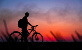 Silhouette of cyclist on the background of red sunset. Biker with bicycle on the field during sunrise Stock Images